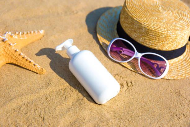 Crème solaire, chapeau de paille et lunettes de soleil sur une plage