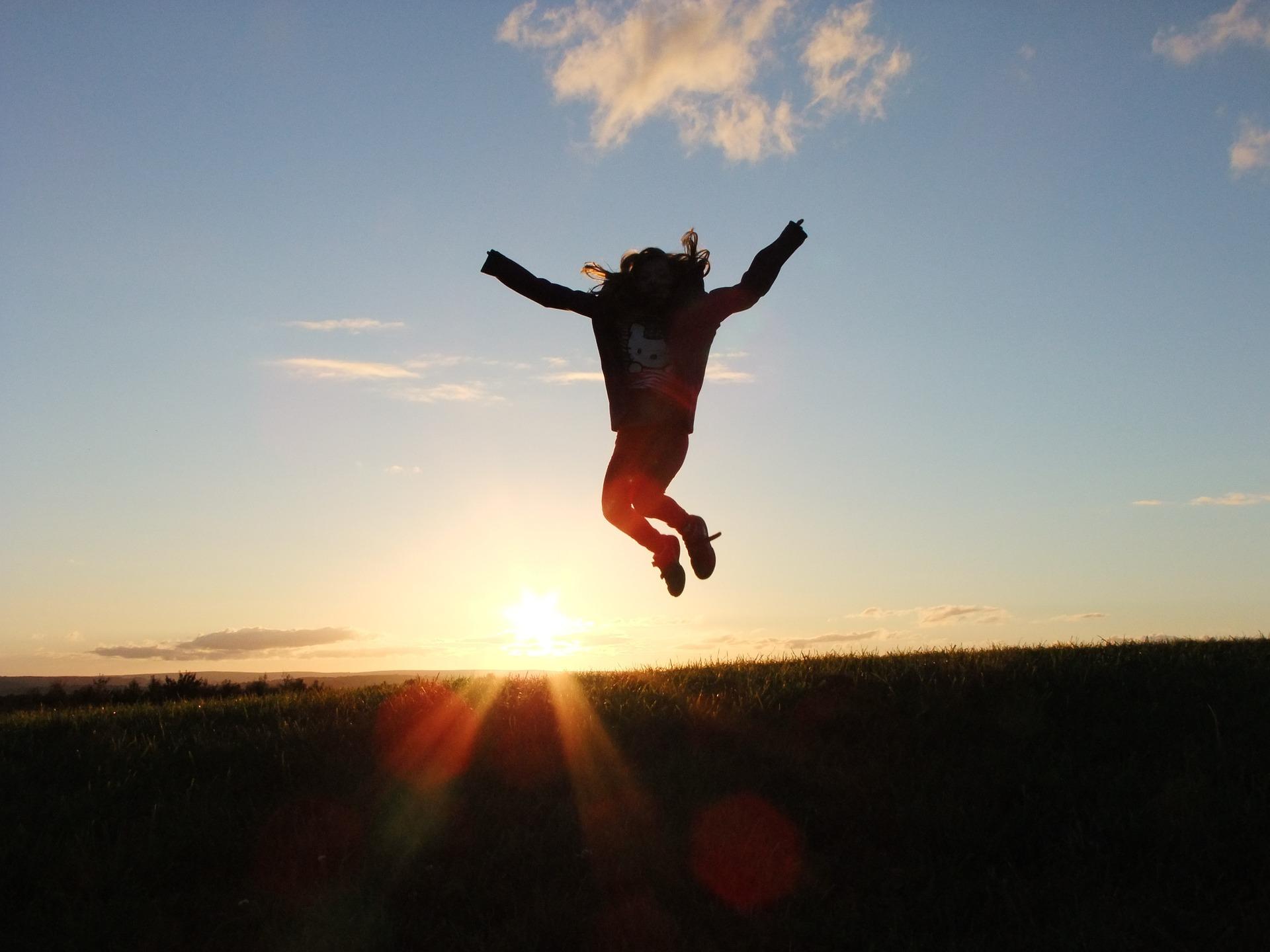 Personne qui saute en l'air au coucher du soleil
