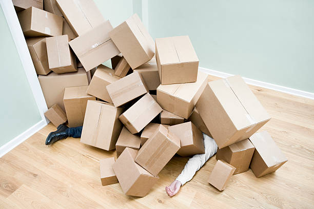 Homme enseveli sous les cartons de déménagement après être tombé par terre