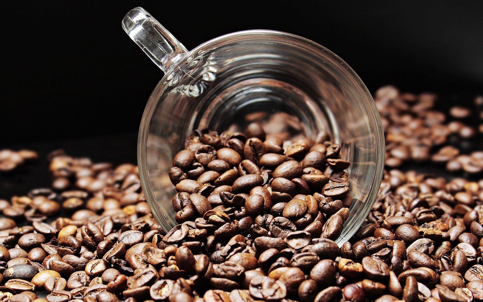 Tasse renversée sur un tas de grains de café
