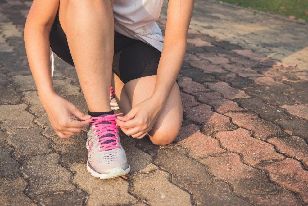 Jeune femme qui lace ses baskets de sport avant d'aller courir